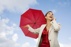 A businesswoman standing underneath an umbrella holding a mobile phone Stock Image
