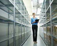 Businesswoman standing in warehouse with clipboard. Portrait of a businesswoman standing in warehouse with clipboard next to metallic shelves and racks Stock Photos