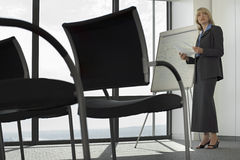 Businesswoman standing beside whiteboard in empty conference room, preparing for presentation Stock Image