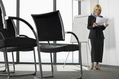 Businesswoman standing beside whiteboard in empty conference room, preparing for presentation Royalty Free Stock Photo