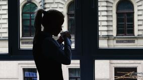 Businesswoman standing at the window after a busy stock video footage