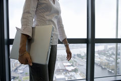 Businesswoman standing beside window, carrying laptop underarm, side view, mid-section Royalty Free Stock Images