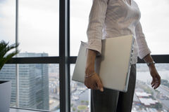 Businesswoman standing beside window, carrying laptop underarm, side view, mid-section Stock Images