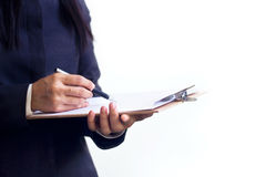 Businesswoman standing writing in planner on white background Stock Photo