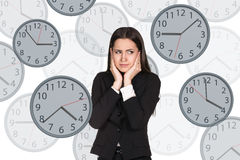 Businesswoman stands among clocks. Royalty Free Stock Image