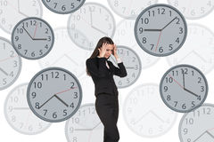 Businesswoman stands among clocks. Stock Photography