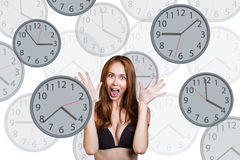 Businesswoman stands among clocks. Royalty Free Stock Photos
