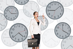 Businesswoman stands among clocks. Stock Images
