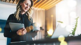 Businesswoman stands in front of computer and looks at screen while drinking coffee, holding digital tablet.Girl working. Young smiling businesswoman in black Stock Image