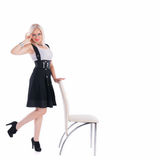 Businesswoman stands near a chair. Thinking of something at the white background stock photography