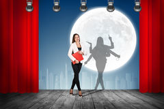 Businesswoman stands on the scene with curtains Royalty Free Stock Images
