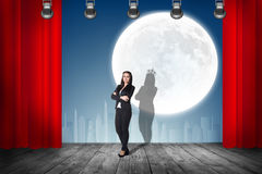 Businesswoman stands on the scene with curtains Royalty Free Stock Image