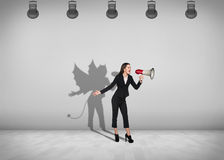 Businesswoman stands with shadow on the wall Royalty Free Stock Images