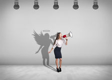 Businesswoman stands with shadow on the wall Royalty Free Stock Image
