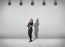 Businesswoman stands with shadow on the wall. Businesswoman stands in the middle of the room with shadow on the wall Stock Photography
