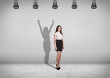 Businesswoman stands with shadow on the wall. Businesswoman stands in the middle of the room with shadow on the wall Stock Image