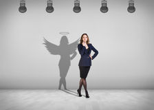 Businesswoman stands with shadow on the wall. Businesswoman stands in the middle of the room with shadow on the wall Stock Images
