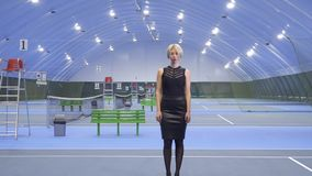 Woman emerges from dark. Businesswoman stands at the tennis court in the dark. The lamps turns on one by one to the end of the big tennis court stock video