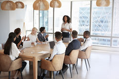Businesswoman Stands To Address Meeting Around Board Table Stock Photography