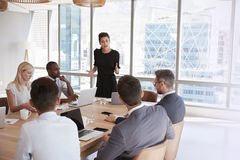 Businesswoman Stands To Address Meeting Around Board Table stock image