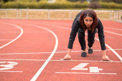 Businesswoman in a Start Position on Race Track. Young Afro-American Businesswoman Looking at the Camera While in a Start Position on Race Track Stock Photography