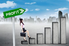 Businesswoman stepping on profit graph. Young businesswoman climbing staircase with profit word on the signpost, shot outdoors Stock Image