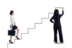 Businesswoman stepping up on stairs to success. Businesswoman stepping up on stairs to gain her success with businesswoman drawing the stairs Royalty Free Stock Photos