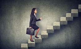 Businesswoman stepping up a stairway career ladder. Businesswoman with briefcase stepping up a stairway career ladder Stock Photography