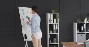 Businesswoman sticking and removing adhesive notes from whiteboard. Young businesswoman sticking and removing adhesive notes from whiteboard at office stock video footage