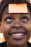 Businesswoman with sticky note. Smiling African American businesswoman with post it reminder note on forehead - focus on eyes Stock Photography