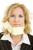 Businesswoman with sticky note. Attractive young blond businesswoman with blank adhesive or sticky notes on face, white background Stock Image