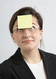 Businesswoman With Sticky Note. Funny businesswoman with yellow sticky note on forehead royalty free stock photography