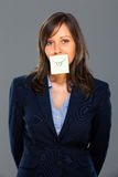 Businesswoman with sticky note. On gray background Royalty Free Stock Photo