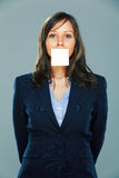 Businesswoman with sticky note. On gray background Royalty Free Stock Image