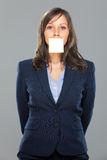 Businesswoman with sticky note. On gray background Stock Photo