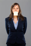 Businesswoman with sticky note. On gray background Stock Images