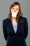 Businesswoman with sticky note. On gray background Stock Photos