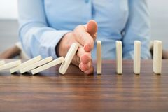 Businesswoman stopping the effect of domino Stock Photos
