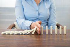 Businesswoman stopping the effect of domino Royalty Free Stock Photography