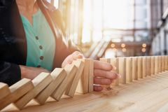 Businesswoman stops a chain fall like domino game. Concept of preventing crisis and failure in business. royalty free stock photography