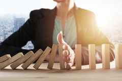 Businesswoman stops a chain fall like domino game. Concept of preventing crisis and failure in business. stock image