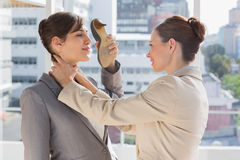 Businesswoman strangling another who is defending with her shoe Royalty Free Stock Photo