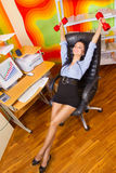 Businesswoman stretching with dumbbells. Office portrait of beautiful businesswoman stretching with dumbbells at her workplace Stock Photos