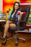 Businesswoman stretching with dumbbells. Office portrait of beautiful businesswoman stretching with dumbbells at her workplace Royalty Free Stock Photography