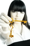 Businesswoman stretching gold keys Stock Photo