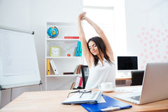 Businesswoman stretching hands in office Stock Photography