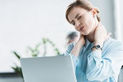 businesswoman suffering from ache in neck while working stock photo
