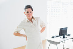 Businesswoman suffering from back ache in office Royalty Free Stock Images