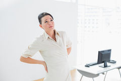 Businesswoman suffering from back ache in office Stock Image