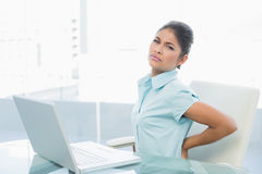 Businesswoman suffering from back ache in office Stock Images